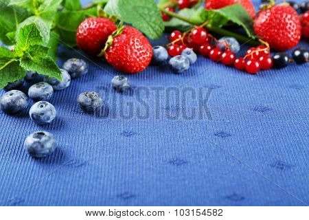 Group of fresh summer berries with mint on blue tablecloth background