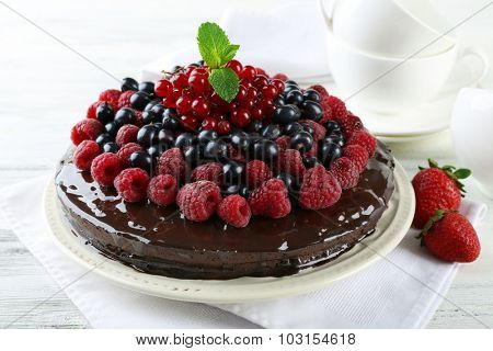 Delicious chocolate cake with summer berries on wooden table, closeup
