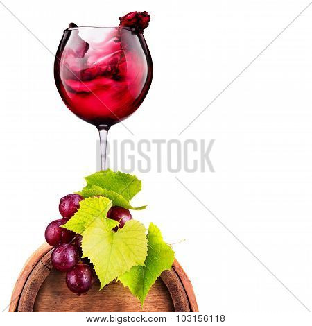 Glass of red wine on a wooden barrel with grape