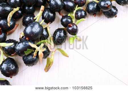 Pile of wet black currants on wooden table, closeup