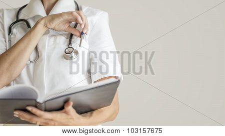 Front View Of Female Doctor With Stethoscope Around Her Neck  About To Take A Pen From A Pocket Of H