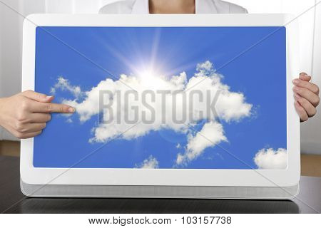 Hands holding tablet PC with sky in screen. Cloud computing concept