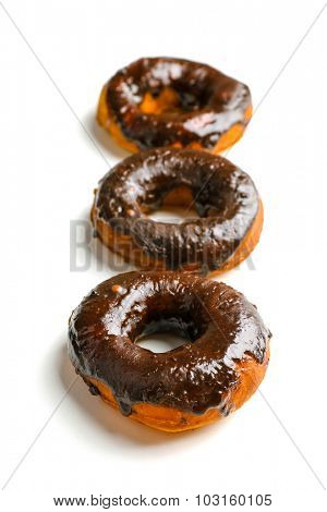 Delicious doughnuts with chocolate icing isolated on white