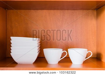 Organized minimalistic kitchen cabinet with white porcelain bowls and cups