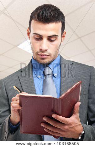 Confident businessman writing on his agenda