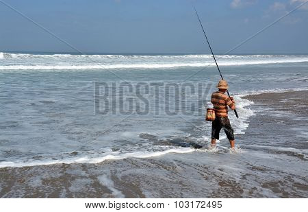 Balinese Fisherman Surf Casting On Legian Beach.