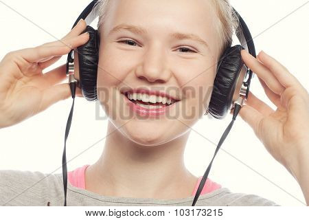 Beautiful happy little girl with headphones. Isolated on white.