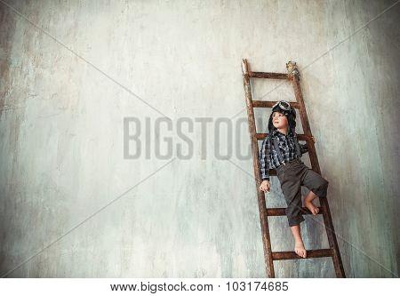 Little boy in a helmet on the ladder