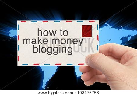 Hand Holding Envelope With How To Make Money Blogging Word On World Background