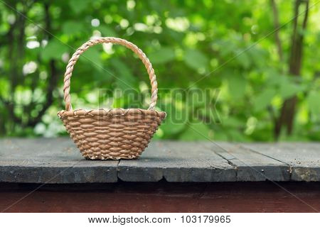 wicker basket on old wooden table and green leaves