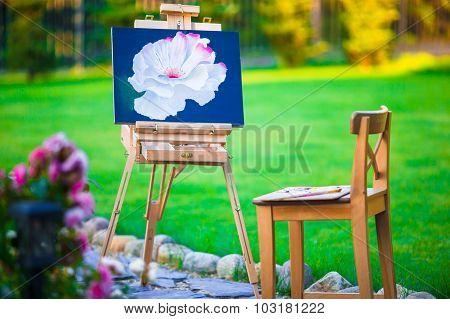 Closeup an easel with beautiful picture in beautiful garden