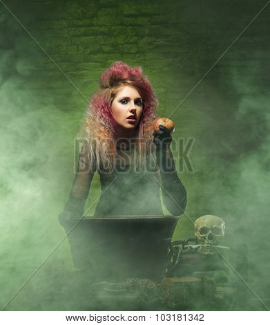 Halloween concept: witch conjuring in a dungeon over green background.