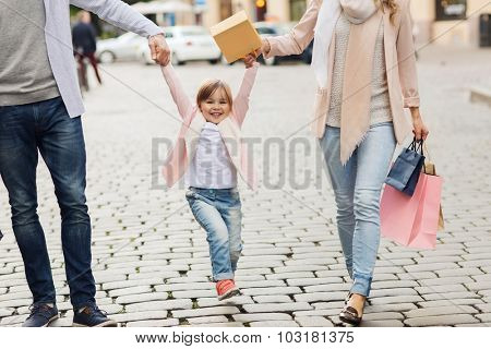 sale, consumerism and people concept - happy family with little child and shopping bags in city