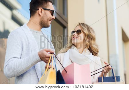 sale, consumerism and people concept - happy couple with shopping bags at shop window on city street