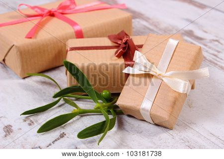 Wrapped Gift For Christmas And Mistletoe On Old Wooden Background