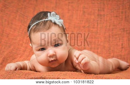 two-month-old girl with decoration on a head lies on a orange background