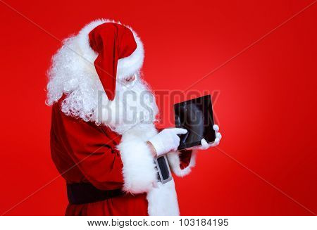 Modern Santa Claus using tablet pc over red background. Christmas.