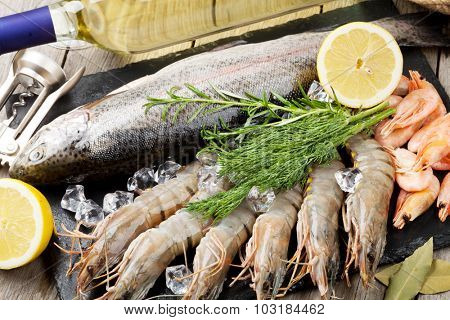 Fresh raw sea food with spices and white wine on wooden table background