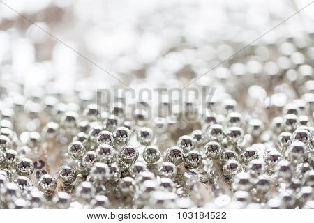 sewing, texture, background, christmas and holiday decoration concept - close up of silver beads on sparkling sequined textile texture