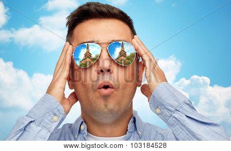travel, tourism, sightseeing, emotions and people concept - face of man in sunglasses with eiffel tower reflection over blue sky and clouds background