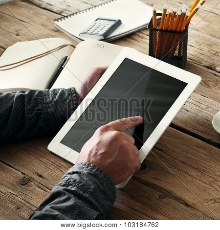 Men Hand Clicks On The Tablet Screen On Wooden Background