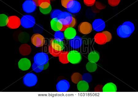 holidays, illumination and electricity concept - colorful bright bokeh night lights over black background
