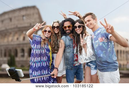 summer vacation, travel, tourism, technology and people concept - smiling young hippie friends taking picture by smartphone selfie stick over coloseum background