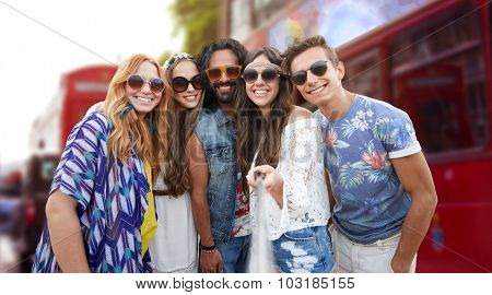 summer vacation, travel, tourism, technology and people concept - smiling young hippie friends taking picture by smartphone selfie stick over London city street background