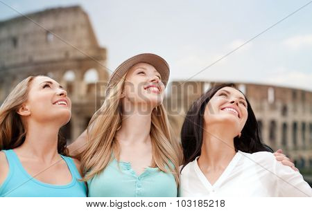 summer holidays, people, travel, tourism and vacation concept - group of smiling young women over coloseum in Rome background