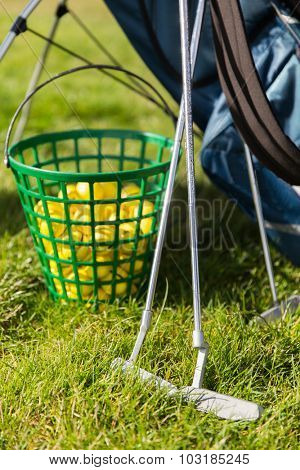 game, entertainment, sport and leisure concept - close up of golf clubs and balls in basket on grass