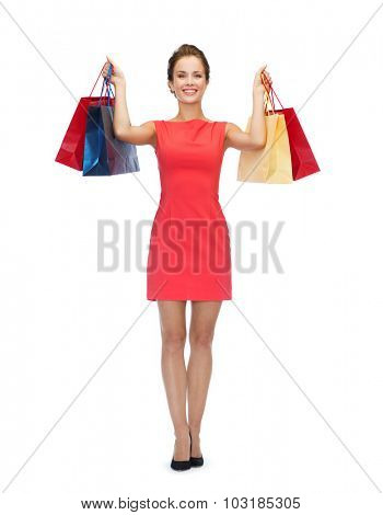 shopping, sale, people, gifts and holidays concept - smiling woman in red dress with shopping bags