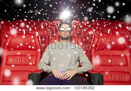 cinema, technology, entertainment and people concept - young man in 3d glasses watching movie alone in empty theater auditorium with snowflakes