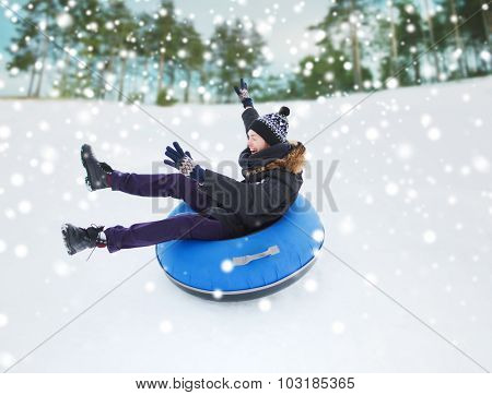 winter, leisure, sport, and people concept - happy teenage boy or young man sliding down on snow tube