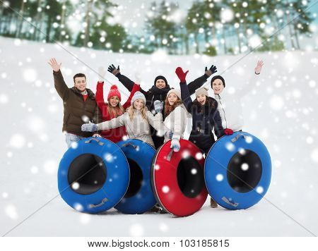 winter, leisure, sport, friendship and people concept - group of smiling friends with snow tubes waving hands outdoors