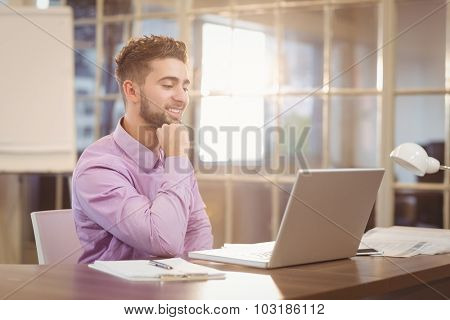 Happy handsome businessman with hand on chin working with laptop in office