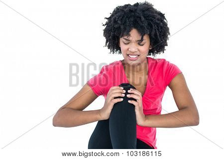 Young woman massaging knee while sitting against white background