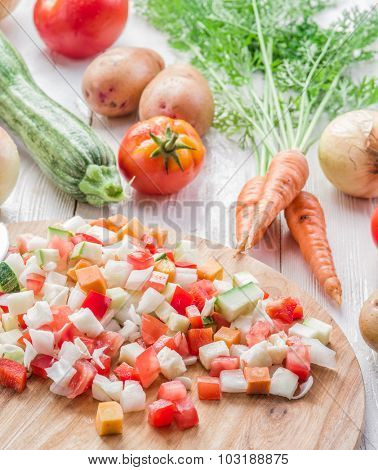 Fresh cut vegetables on the wooden chopping board.