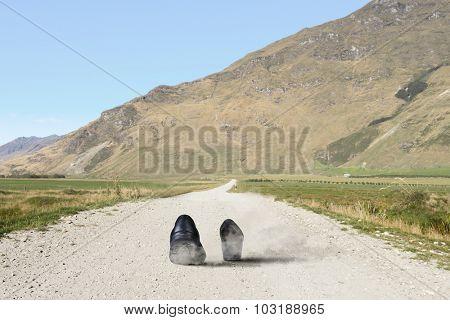 Pair of black shoes walking on road