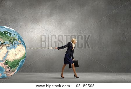 Young businesswoman with suitcase pulling Earth planet with lead. Elements of this image are furnished by NASA