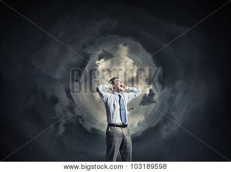 Frustrated businessman screaming emotionally with hands on head
