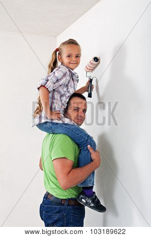Father and daughter painting the room together - having fun together