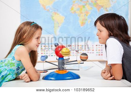 Kids with a scale model planetary system in geography science class discussing