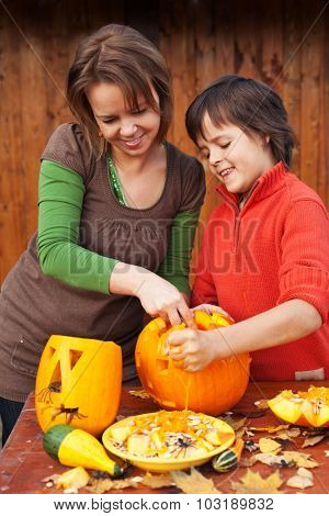 Young boy and woman carving a jack-o-lantern - preparing for halloween