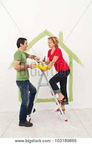 Young couple  creating their new home - drawing the conceptual blueprints