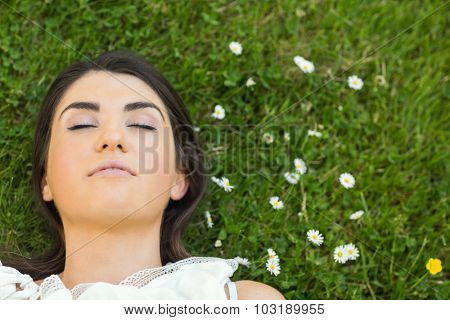 Beautiful young woman relaxing with eyes closed on grassland in park