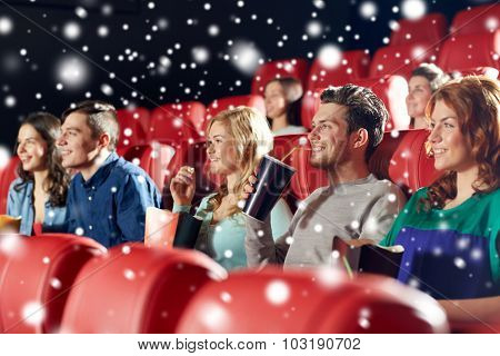 cinema, entertainment and people concept - happy friends with popcorn and lemonade drinks watching movie in theater with snowflakes