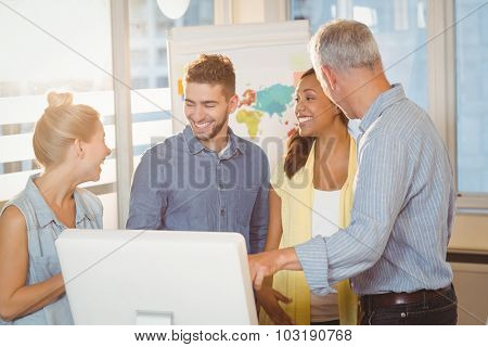 Smiling business people using computer in meeting room at creative office