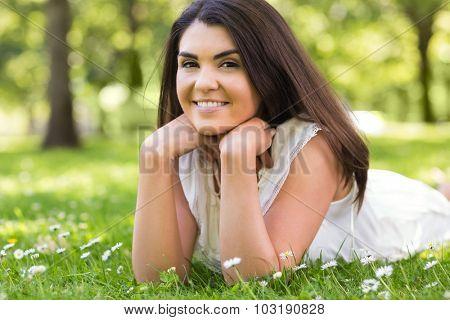 Portrait of pretty cheerful woman lying on grassland in park