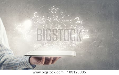 Tablet pc in businessman hand and plan sketches
