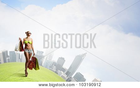 Young pretty woman in bikini and shorts with shopping bags